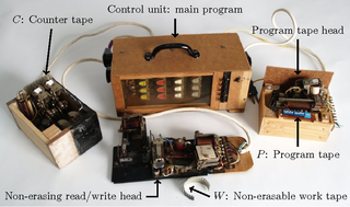 "<p>Hasenjaeger&rsquo;s universal electromechanical Turing machine. The wiring in the control unit encodes a universal program, that uses only four states and two symbols, for simulating Wang B machines. The program of a Wang B machine may be stored on the program tape. There are two additional tapes which are used for the simulation, a counter tape and a work tape.</p> <p>Source:<br /><a href=""https://www.semanticscholar.org/paper/Wang&apos;s-B-machines-are-efficiently-universal%2C-as-is-Neary-Woods/72cf316d3954356650c14346da595ee25cbd169c"" target=""_blank"">www.semanticscholar.org</a></p>"